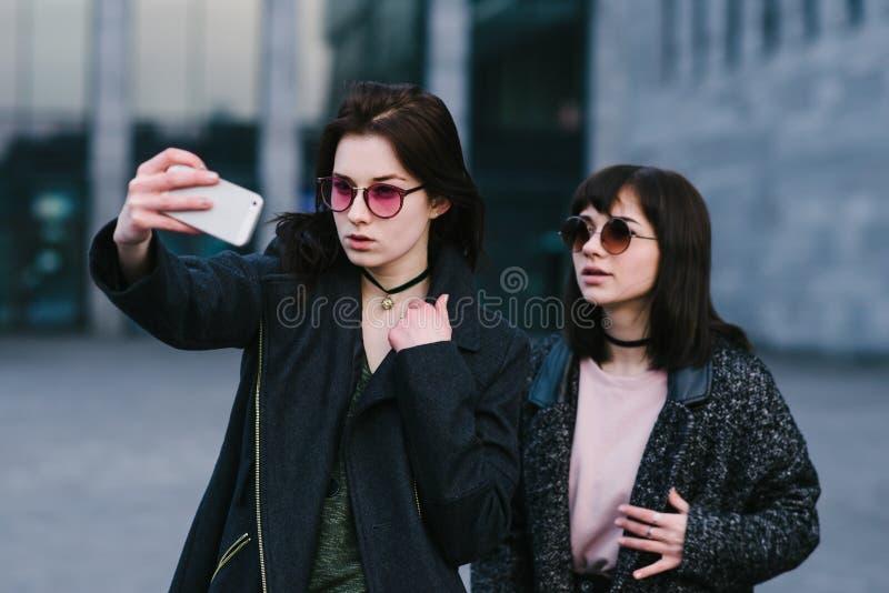 Porträt von zwei stilvoll gekleideten Mädchen, die selfie vor dem hintergrund eines schönen Stadtbilds tun lizenzfreie stockfotografie