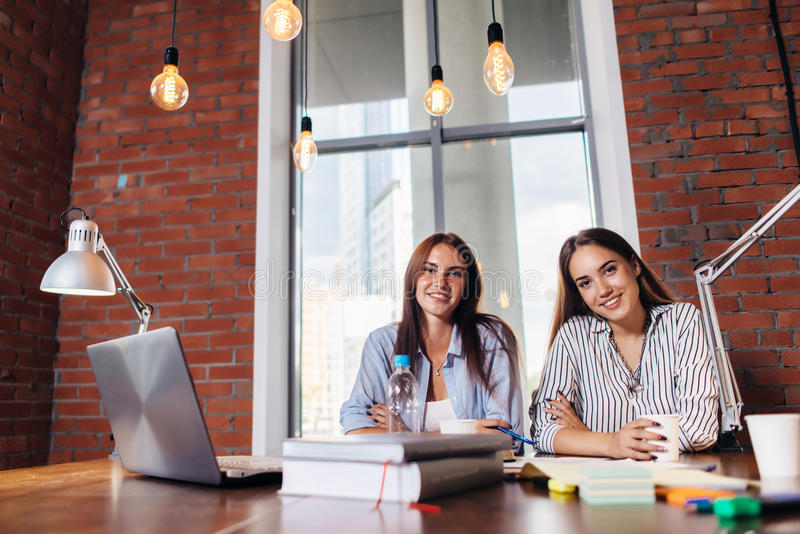 Porträt von zwei Studentinnen, die, sitzend am Schreibtisch lächeln und betrachten die Kamera, die für Lektionen sich vorbereitet stockfotos