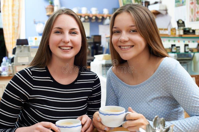 Porträt von zwei weiblichen Jugendfreunden, die im Café sich treffen lizenzfreie stockfotografie