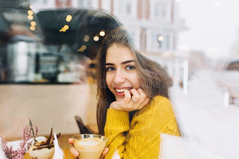 Porträt, welches die junge Frau mit freundlichem Lächeln, langes brunette Haar lächelnd im Fenster des Cafés in der Winterzeit be stockfotografie