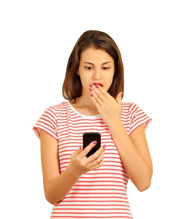 Porträt wenn ein entsetztes junges Mädchen, das Handy betrachtet emotionales Mädchen lokalisiert auf weißem Hintergrund lizenzfreie stockfotos