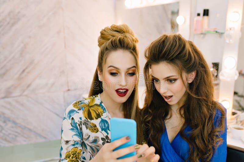 Portr?t zwei erstaunte die h?bschen Frauen, die Telefon im Sch?nheitssalon betrachten Spa?, Klatschm?dchen, bereitend zur Partei  stockfoto
