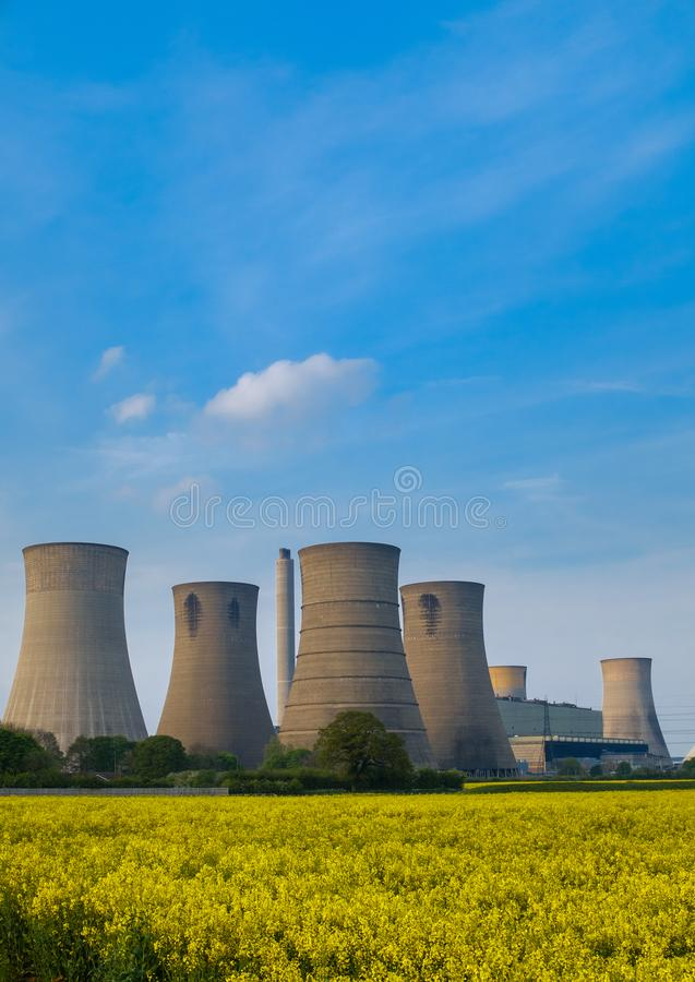 Porträtaufnahme von Kühltürmen eines Kohle getankten Kraftwerks im Vordergrund ist ein helles gelbes Feld des Blühens stockfotos