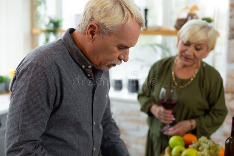 Porträtfoto des hübschen attraktiven Silber-haarigen Ehemanns, der Nahrung kocht stockfotografie