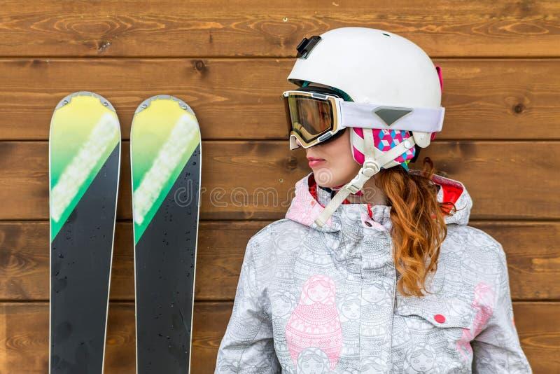 Porträtfrauenskifahrer mit Skis und Sturzhelm nahe hölzerner Wand lizenzfreies stockbild