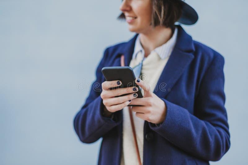 Porträtfreien einer jungen Schönheit mit der stilvollen Kleidung, die mit einem modernen Hut aufwirft und Handy verwendet lebenss lizenzfreie stockfotografie