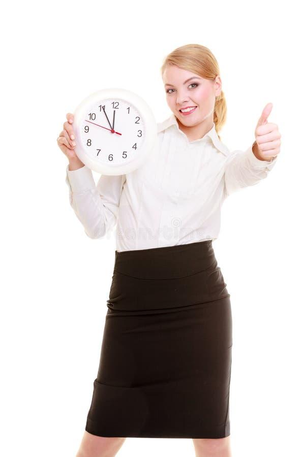 Porträtgeschäftsfrau, die sich Uhr und Daumen zeigt. Zeit. stockfotos