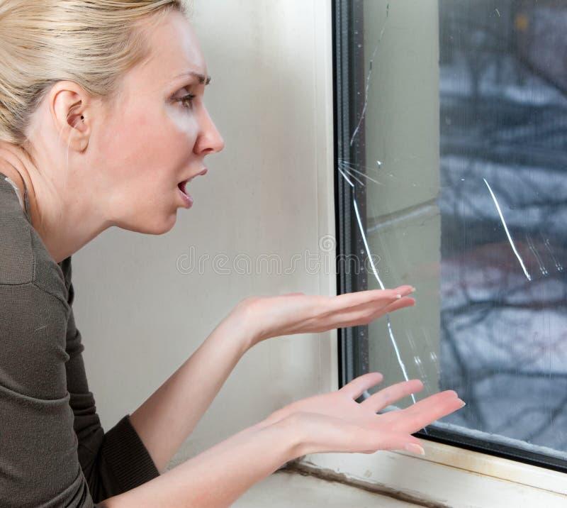 Porträthausfrau am Fenster, die von einem Frost mit einem doppelverglasten Fenster gesprengt haben lizenzfreies stockfoto