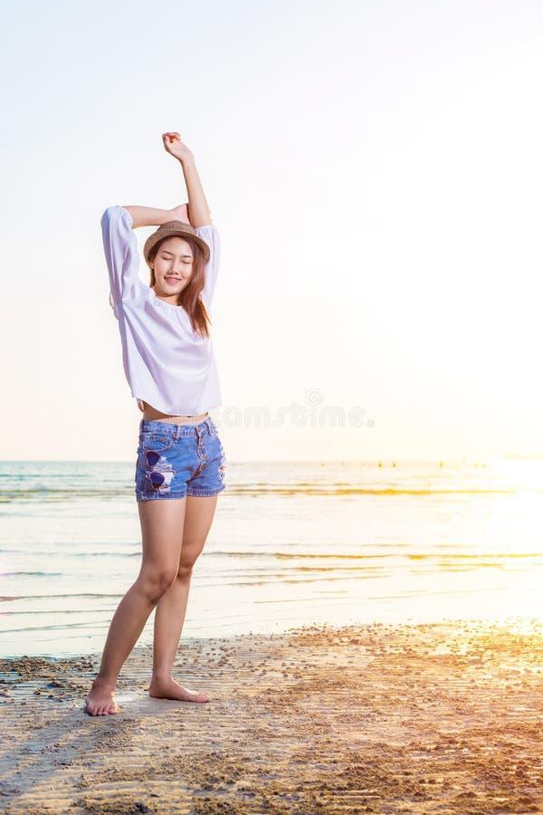 Porträtlächeln-Frauenabnutzungshut und glückliches auf dem Strand stockfotos