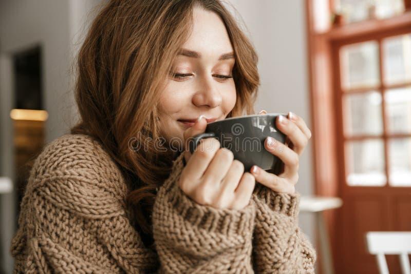 Porträtnahaufnahme der frohen lächelnden Frau in gestrickter Strickjacke, sitti stockfotografie