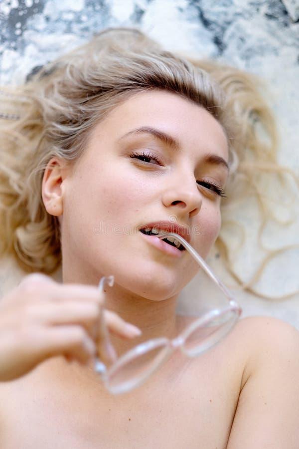 Porträtphotographie einer sexy jungen Frau mit Gläsern und blondes Haar, welche die Gläser in ihrem Mund bügeln lizenzfreies stockbild