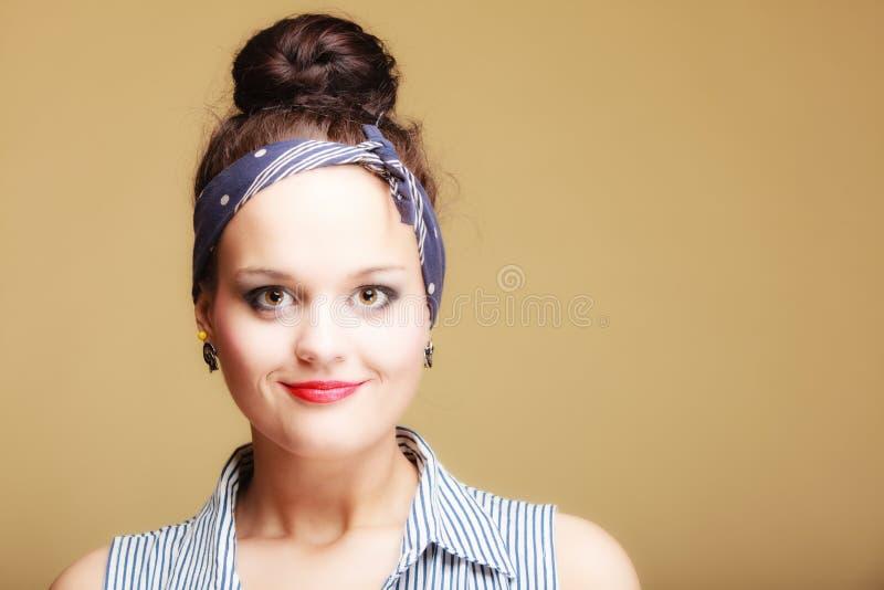 Porträtpin-up-girl mit Brötchen und Hairband auf Braun Art und Weise stockfoto