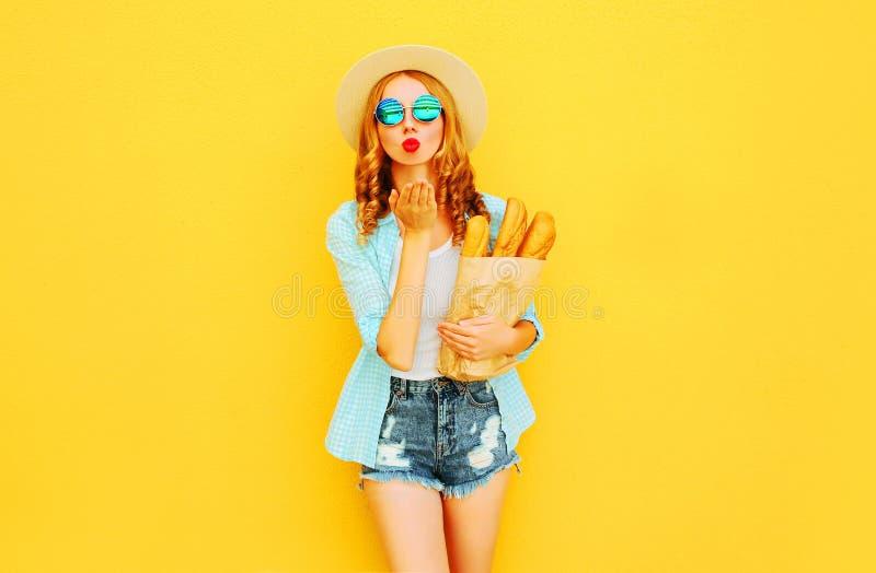 Porträtschönheit, die süße Luftkuss-Holdingpapiertüte mit langem Weißbrotstangenbrot, tragender Strohhut, kurze Hosen sendet stockfotografie