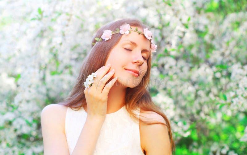 Porträtschönheit mit Blumenstirnband und den Blumenblättern von Blumen lizenzfreie stockbilder