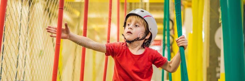 Porträtt av 6-årig pojke med hjälm och klättring Underordnad i abstacle-kurs i äventyrsspelningsbanor, BANNER, LONG royaltyfria foton