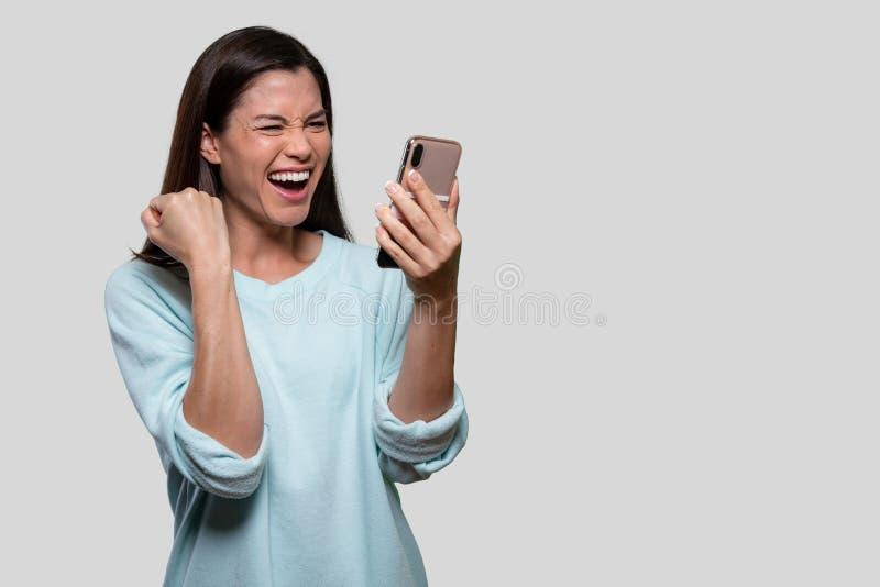 Porträtt av en blandad tävlingskvinna som firar, upphetsar, är en ecstatisk nyhet, håller smartphone, på vit bakgrund royaltyfri bild
