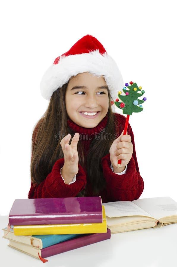 Porträtt av en entusiastisk liten flicka som bar julhatt med böcker royaltyfri foto
