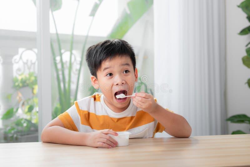 Porträtt av en leende liten pojke som äter giftig yoghurt arkivfoton
