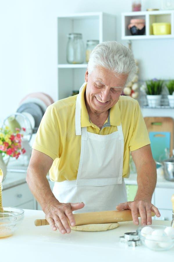 Porträtt av en lycklig äldre man som bakar kakor royaltyfria foton