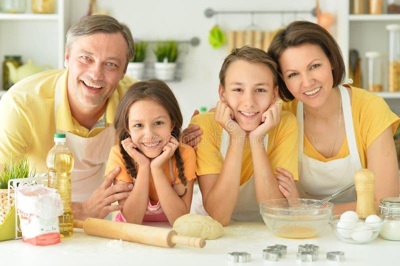 Porträtt av en lycklig familj som bakar tillsammans i köket royaltyfri bild