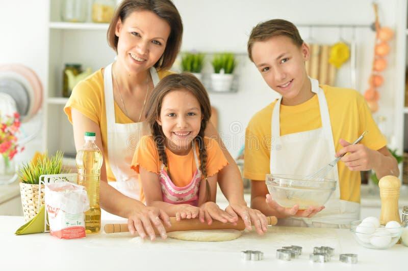 Porträtt av en lycklig familj som bakar tillsammans i köket arkivfoto