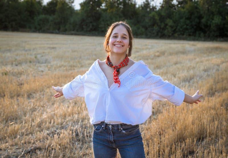 Porträtt av en lycklig flicka på halmfält med utsträckta händer royaltyfri bild