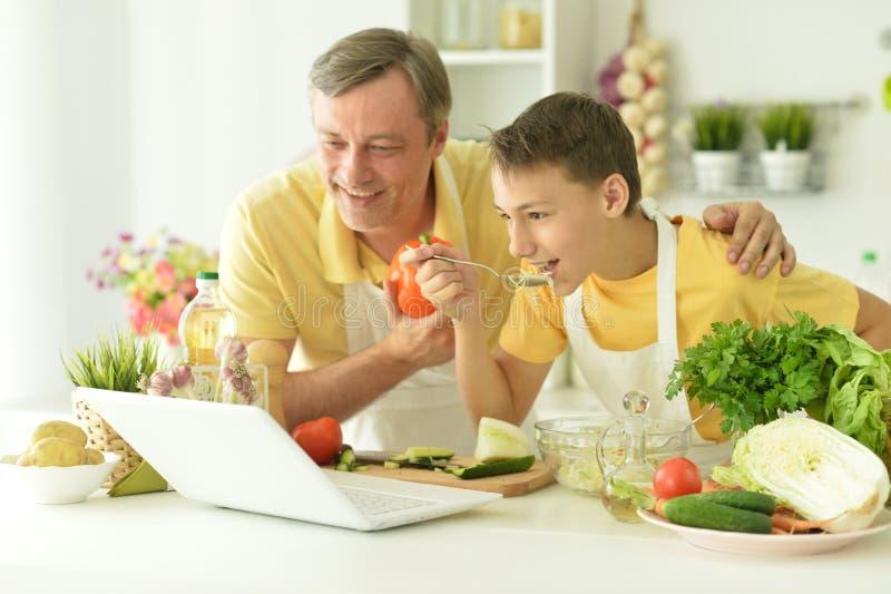 Porträtt av en man och pojke som kokar i köket royaltyfria bilder