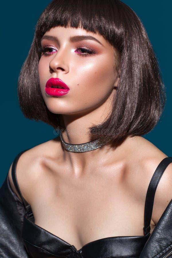 Porträtt av en ung, vacker brunettmodell med färgstark professionell smak, bob-frisyr, röd läppstift och ögoneliner fotografering för bildbyråer