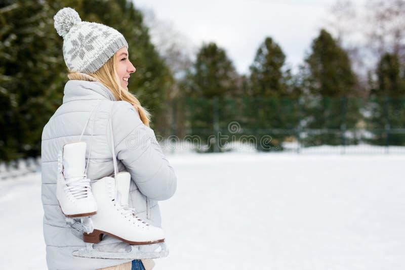 Porträtt av en vacker kvinna som håller isskiffer i vinterparken royaltyfri fotografi