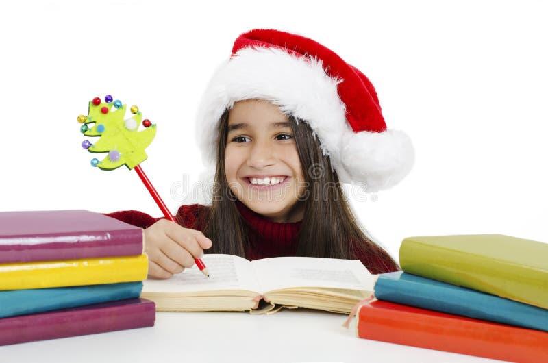 Porträtt av en vacker liten flicka som bar julhatt och läste en bok fotografering för bildbyråer