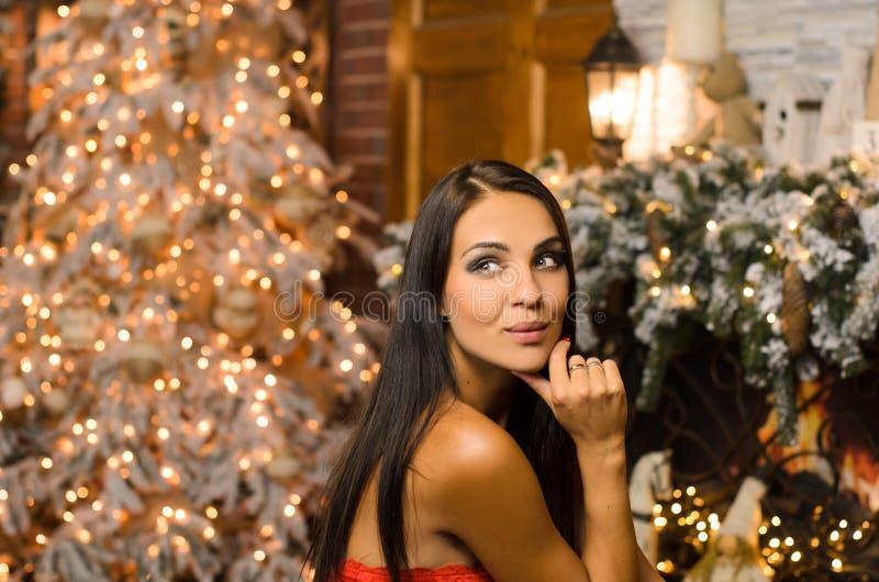 Porträtt av en vacker, lycklig, mörkhårig kvinna, i nyårslinne, i väntan på julhelger, kvällsfotografering, ljus royaltyfri foto