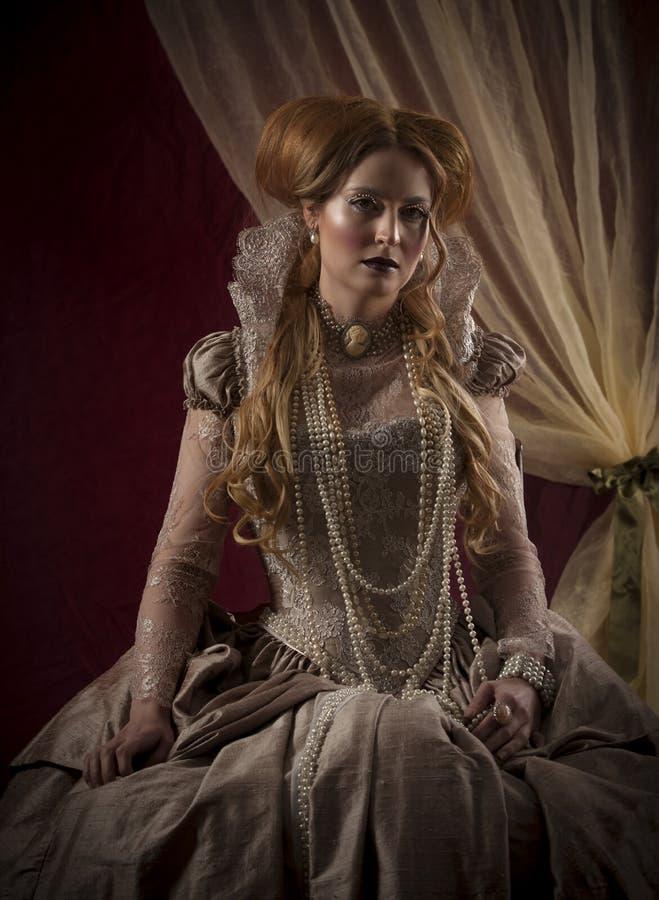 Porträtt av en vacker, röd kvinna klädd i tidsperioder som Elizabeth I royaltyfria foton