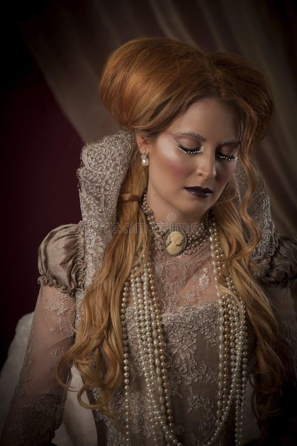 Porträtt av en vacker, röd kvinna klädd i tidsperioder som Elizabeth I royaltyfri bild