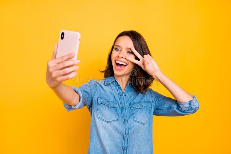 Porträtt av glad positiv fotograf som tar selfie med mobiltelefon på semester, så att v-tecknen har kul royaltyfria foton