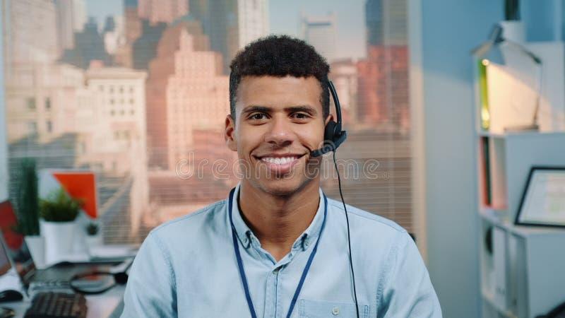 Porträtt av kund- eller serviceansvarig för blandad kapplöpning i ett headset som leker med kameran royaltyfri bild