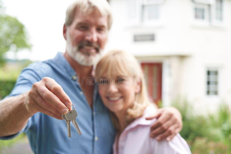 Porträtt av mogenskap par som står i Garden framför Dream Home i lådor arkivbild