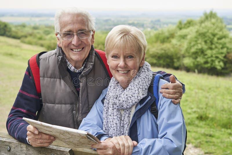 Porträtt av pensionerade par på semester med lucka och karta fotografering för bildbyråer