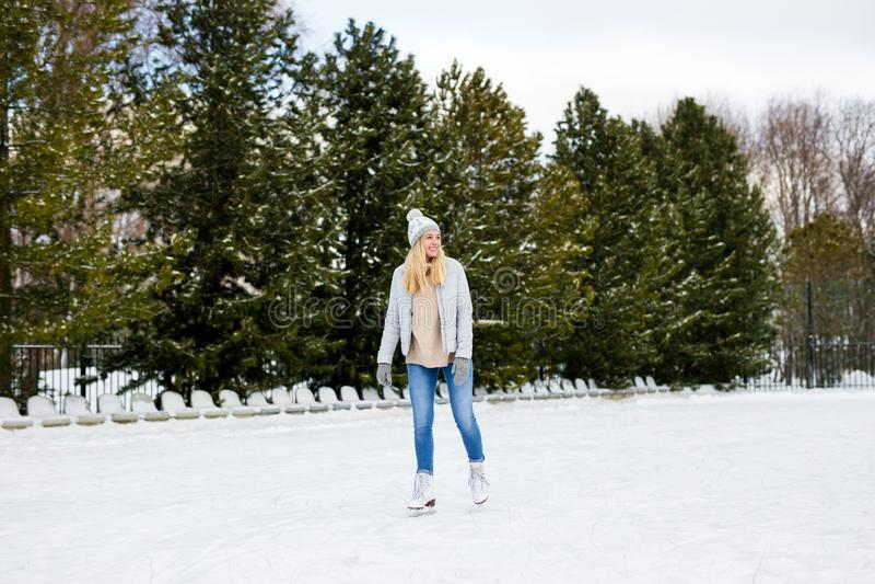 Porträtt av unga kvinnor som skriker på is med bilskridskor utomhus royaltyfri fotografi