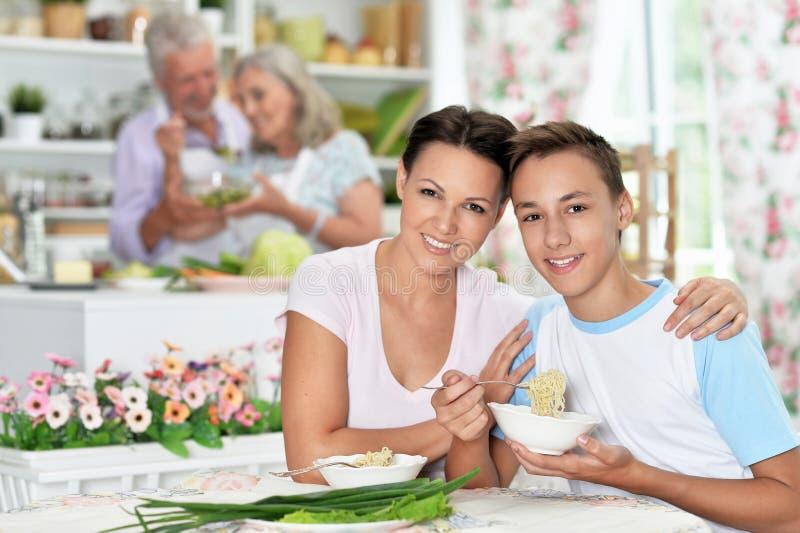 Porträtt från mor och son som äter i köket royaltyfri foto