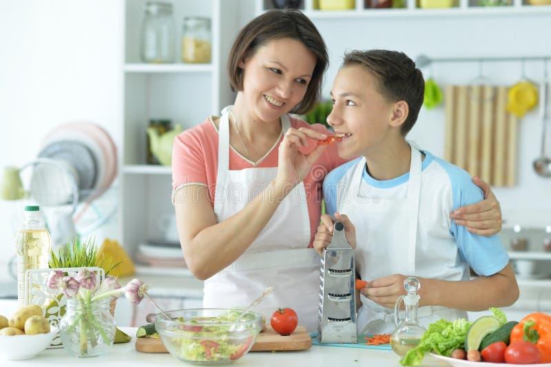 Porträtt från mor och son som gör färsk sallad i köket royaltyfri fotografi