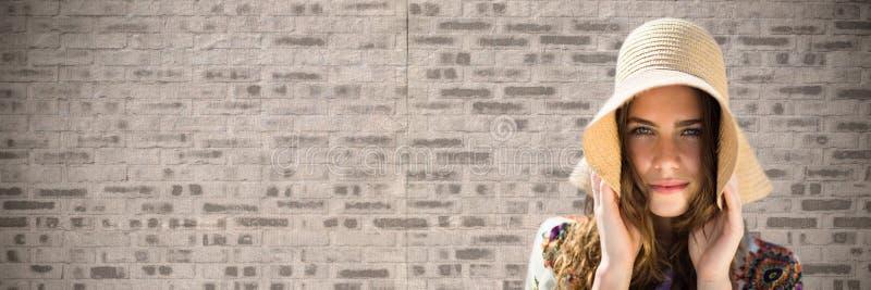 Porträttering av den hållande solhatten för kvinna mot den bruna tegelstenväggen arkivfoto