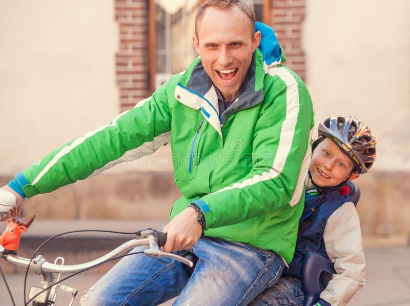 Porträtvater mit Radfahrenfahrrad des Sohns zusammen stockfoto