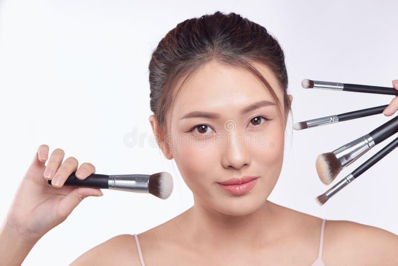 Portr?t attraktiven asiatischen l?chelnden Frau Brunette lokalisiert auf wei?er Atelieraufnahme mit B?rsten f?r Make-up stockfoto