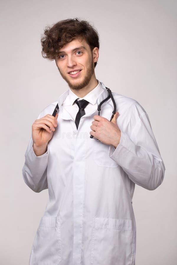 Portr?t ?berzeugten jungen l?chelnden Arztes mit sthetoscope ?ber hellgrauem Hintergrund lizenzfreie stockfotografie