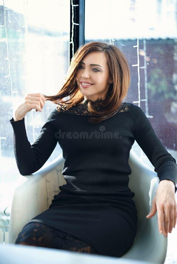 Portr?t, das junge Frau mit freundlichem L?cheln, l?chelndes Caf? des langen brunette Haares bezaubert lizenzfreies stockbild