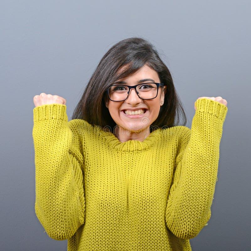 Portr?t der gl?cklichen Frau jubelt die pumpenden ekstatischen F?uste feiert Erfolg gegen grauen Hintergrund lizenzfreie stockfotografie