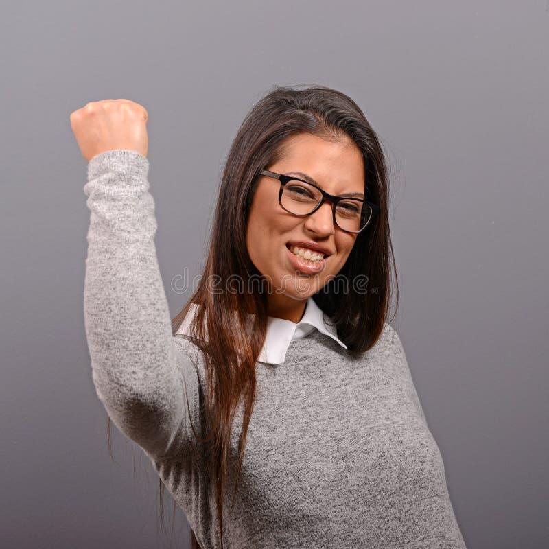 Portr?t der gl?cklichen Frau jubelt die pumpenden ekstatischen F?uste feiert Erfolg gegen grauen Hintergrund lizenzfreies stockfoto