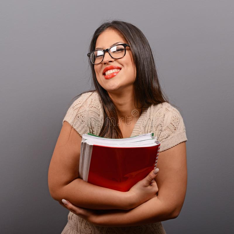 Portr?t der gl?cklichen Studentenfrau, die B?cher gegen grauen Hintergrund h?lt stockfotografie