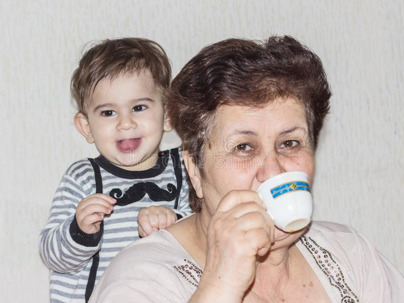 Portr?t der Gro?mutter mit Enkel ein trinkender Kaffee der ?lteren Frau stockbild