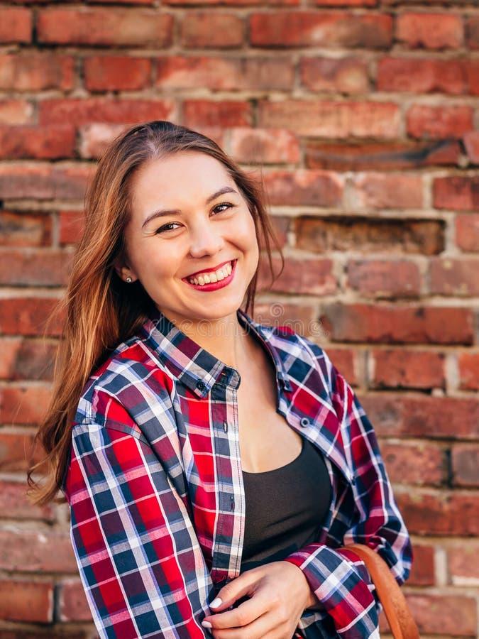 Portr?t der jungen Frau gegen Backsteinmauer lizenzfreies stockbild